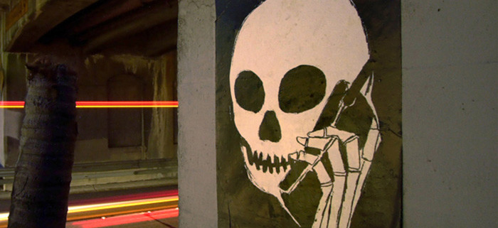 391785 01: A graffiti image of a skull holding a cell phone is painted on an underpass along the Pasadena Freeway, July 11, 2001 in Los Angeles, CA. California state Assemblyman S. Joseph Simitian, a freshman democrat from Palo Alto, plans to reintroduce legislation that would ban hands-on cellular use while driving in California. A similar bill fell one vote shy of clearing a key assembly committee in May. (Photo by David McNew/Getty Images)