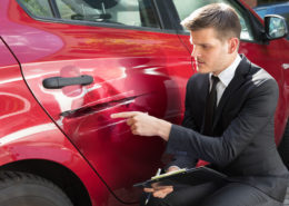 Insurance Agent Filling Insurance Form Near Damaged Red Car