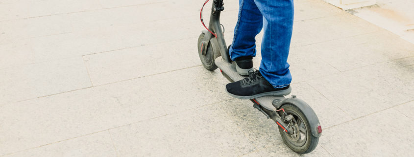 Man in jeans on an electric scooter through the city, copy space, electric urban mobility.