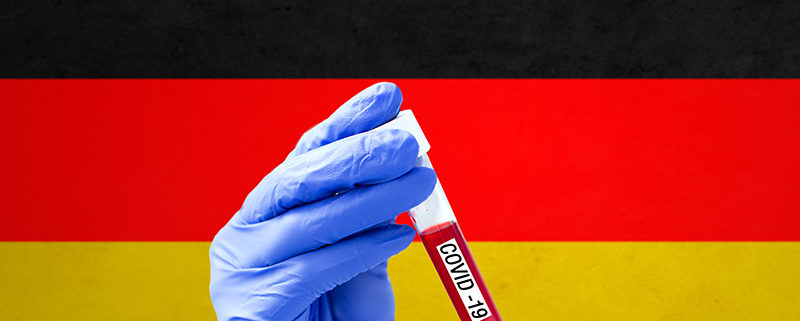 medicine, pandemic and virus concept - close up of hand in protective glove holding test tube with blood sample for coronavirus research over flag of germany on background