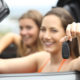 Two happy tourists showing a rental car keys on summer vacations